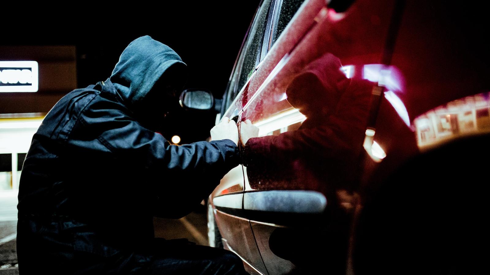 Un voleur de voiture en action tard dans la nuit, portant des vêtements noirs.