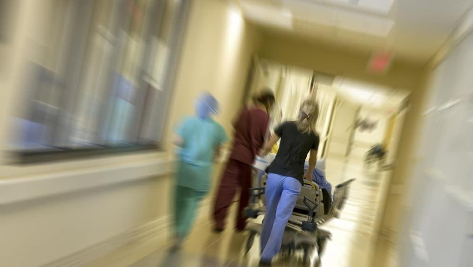 Une infirmière fait rouler un lit dans un couloir d'hôpital.