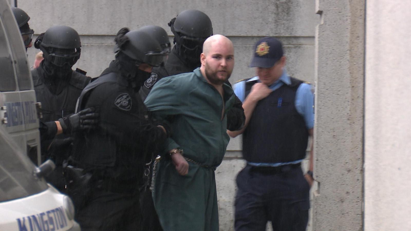 Photo d'un homme menotté habillé en vert qui est escorté par des policiers vêtus de noir.