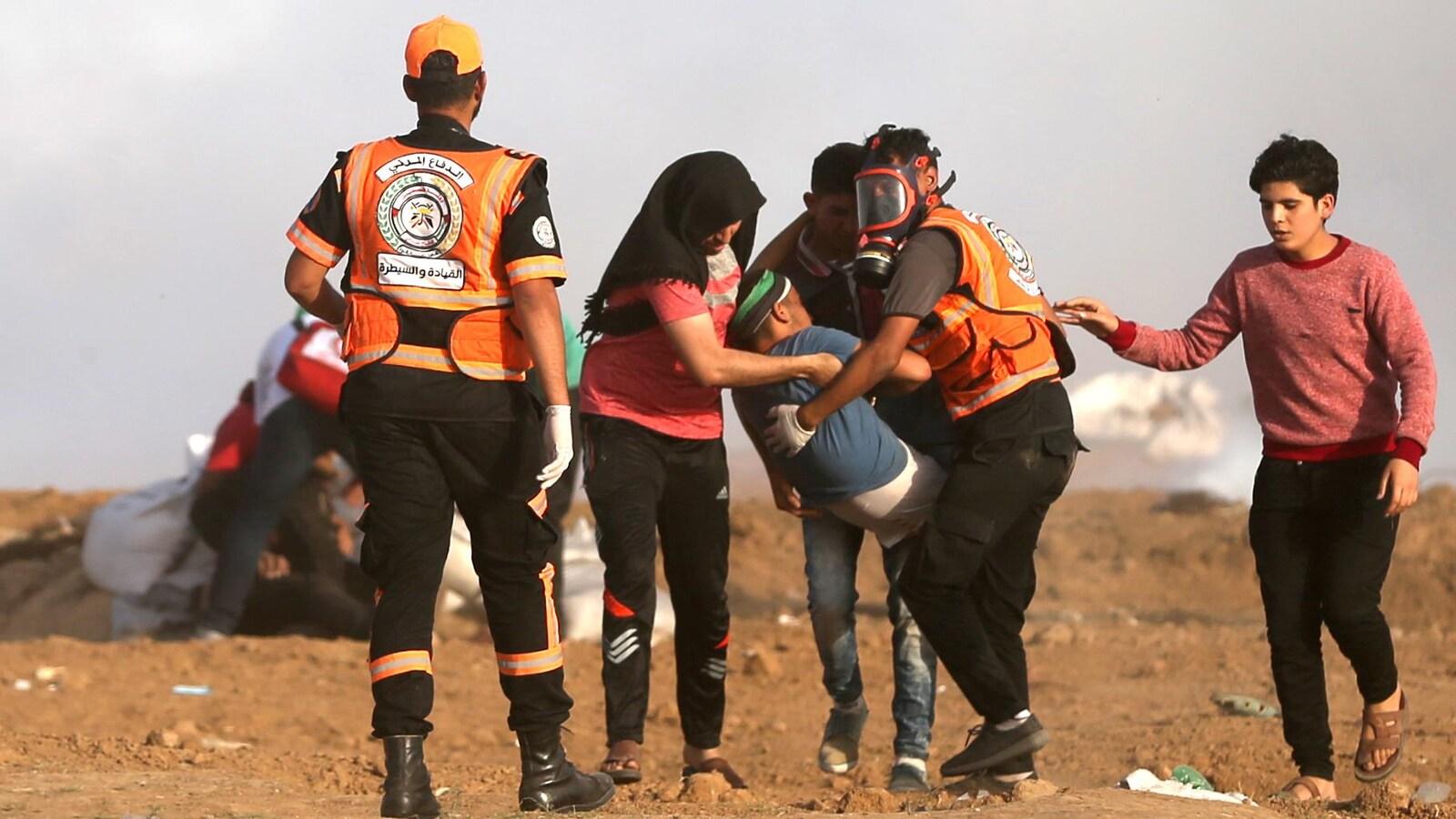 Des hommes et une femme transportent une jeune personne, qui semble inconsciente, dans leurs bras. Un des hommes porte un masque à gaz.