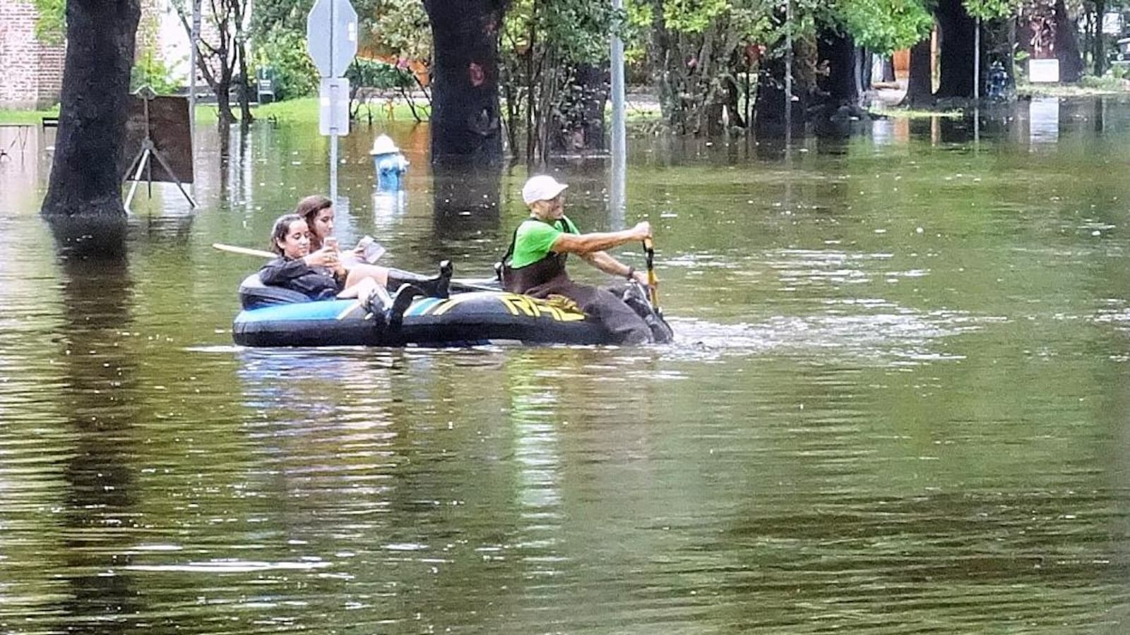 Des sinistrés naviguent dans les rues de Houston à bord d'une petite embarcation gonflable.