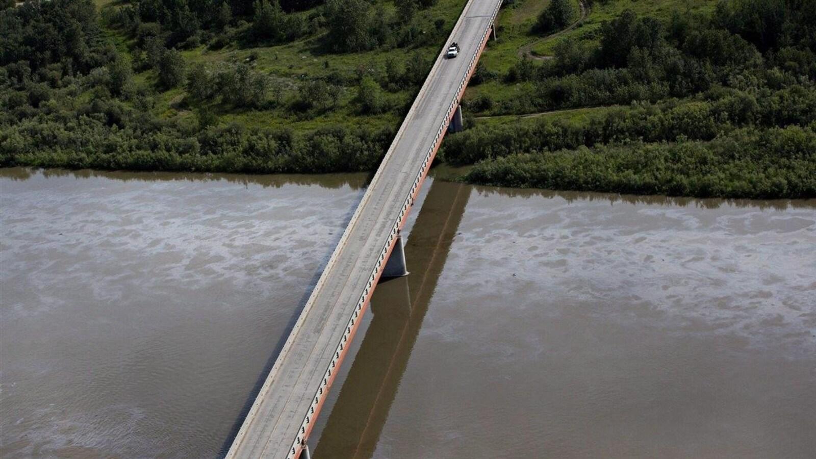 Vue aérienne de la nappe de pétrole sur la rivière Saskatchewan Nord. La rivière coule sous un pont qui mène à une rive boisée.