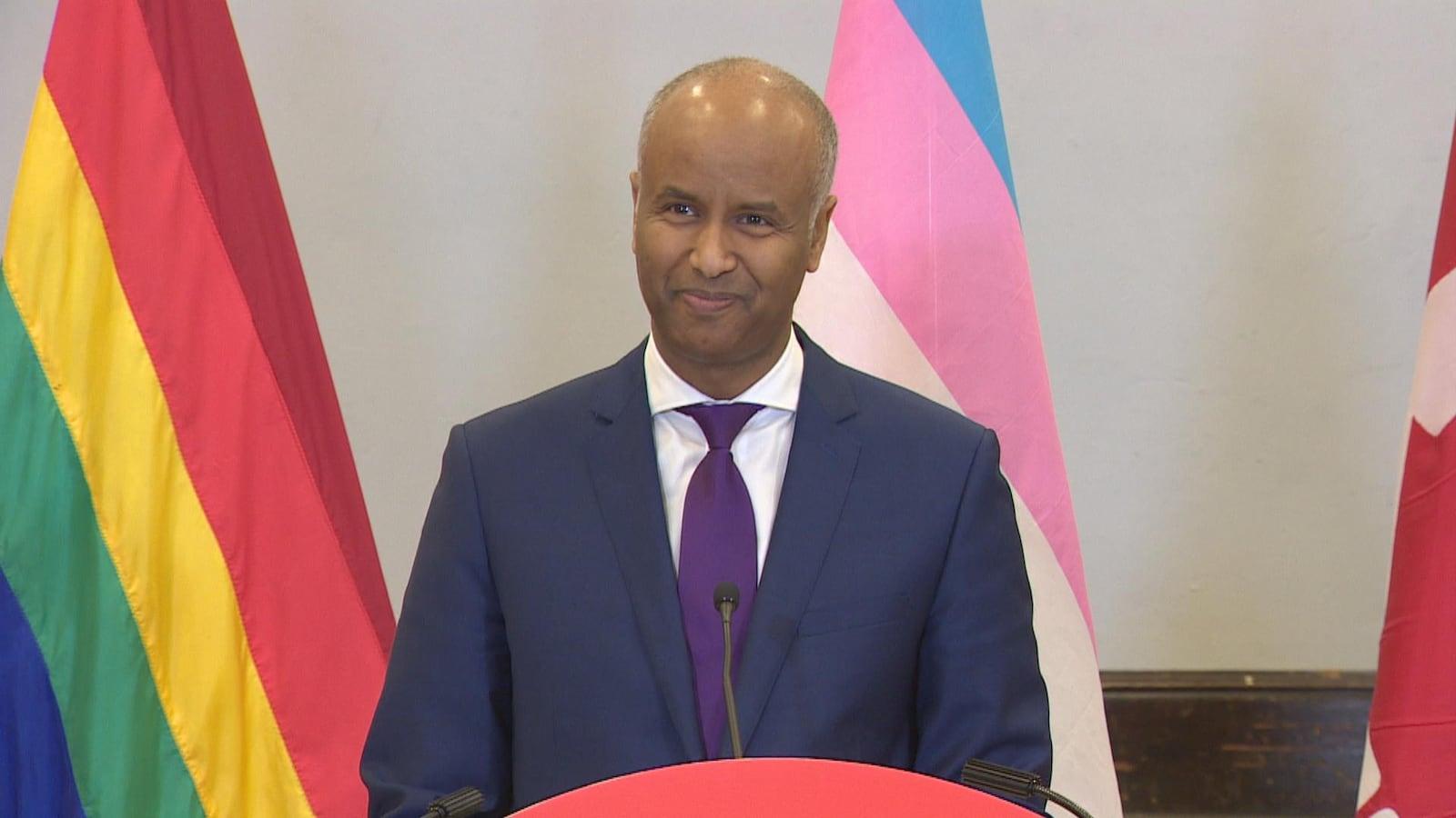 Le ministre Ahmed Hussen parle devant une tribune avec des drapeaux des communautés LGBTQ+ derrière lui.