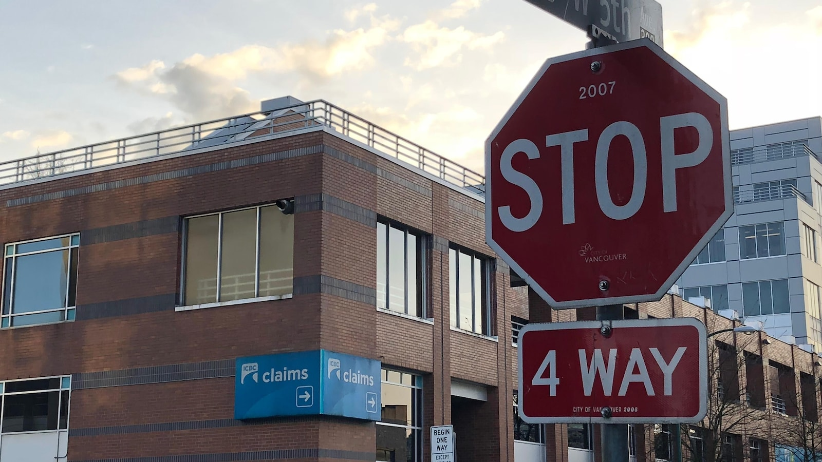 À l'avant-plan, un arrêt de circulation, avec en arrière-plan, de l'autre côté de l'intersection, une affiche d'ICBC qui indique aux gens quel chemin suivre pour aller déposer une réclamation.