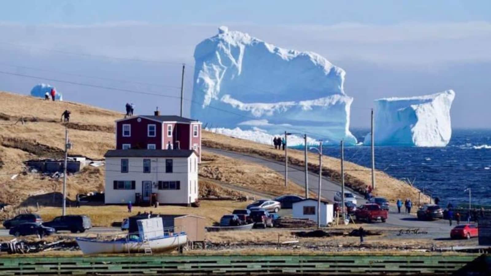 Des voitures immobiles sur la route côtière avec un iceberg en arrière-plan.