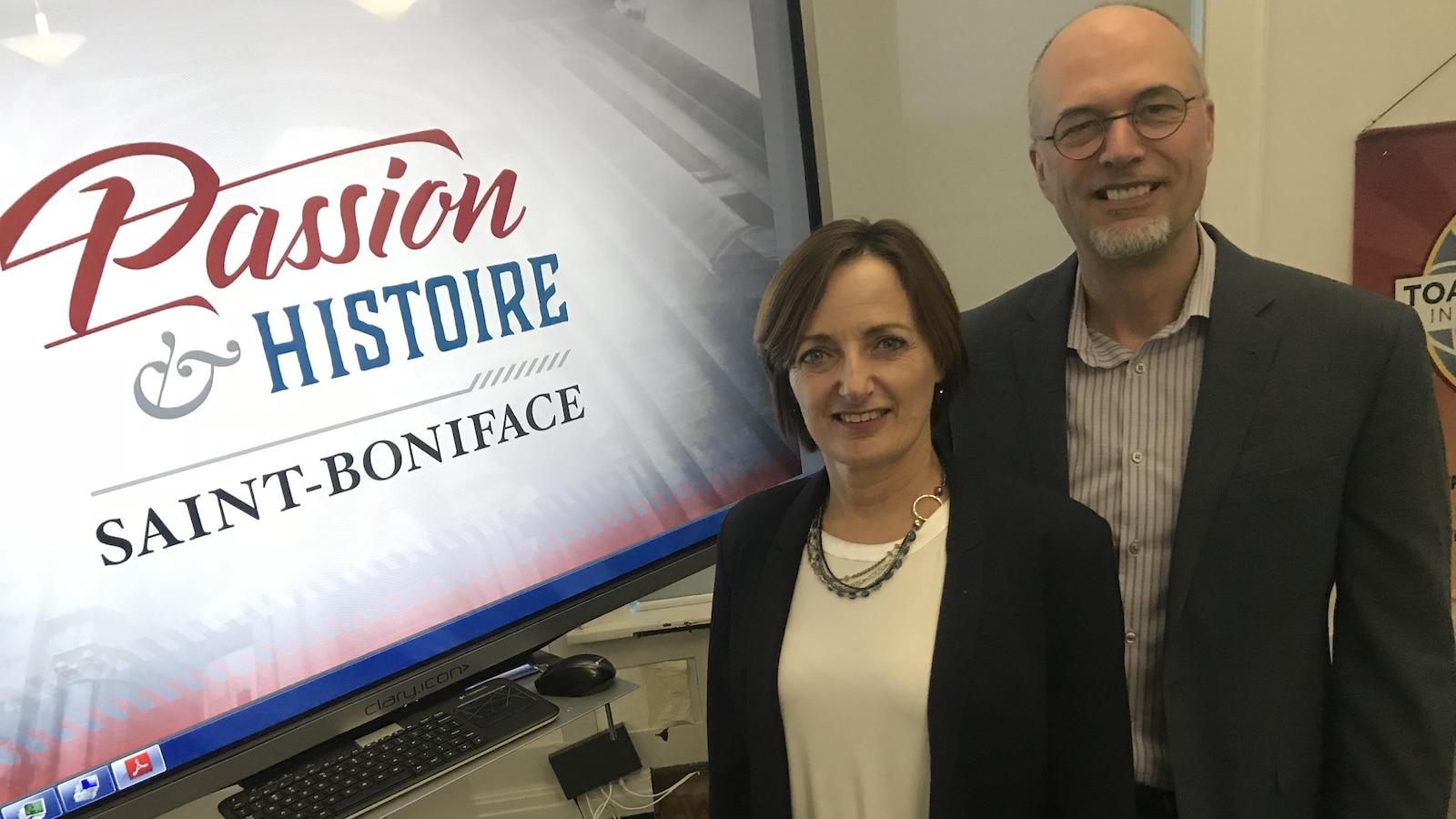 Un homme et une femme sont debout à côté d'un écran où l'on peut lire « Passion et histoire Saint-Boniface».
