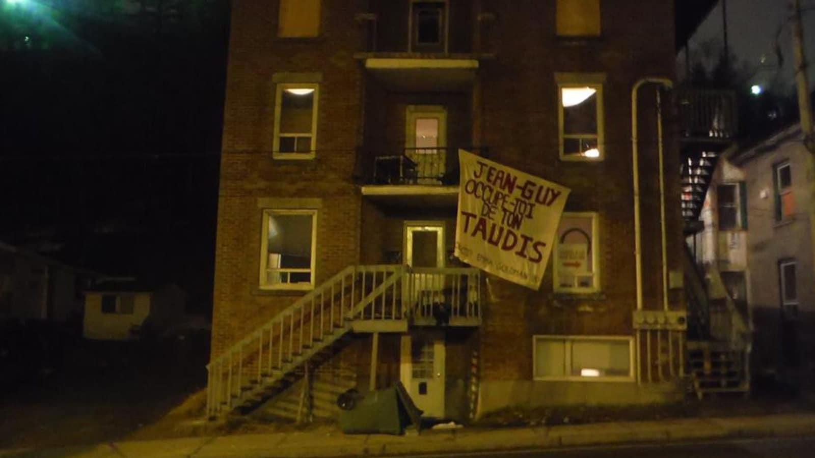 Une affiche qui est inscrit : Jean-Guy, occupe-toi de ton taudis est accroché sur l'immeuble d'un logement.