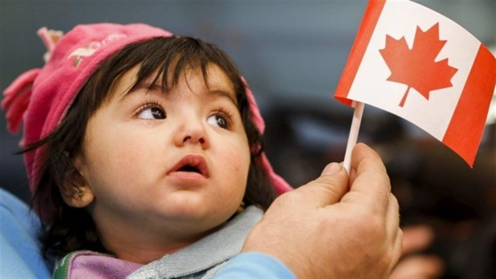 Une jeune réfugiée syrienne regarde un petit drapeau du Canada.