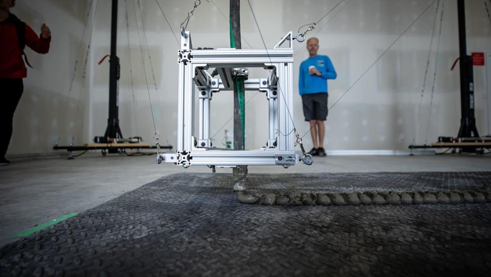 Une machine en forme de cube qui dépose du béton au sol.
