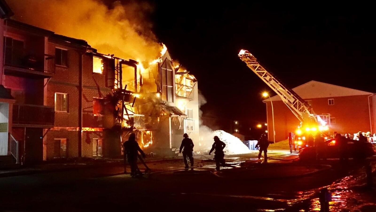 Des pompiers arrivent sur les lieux de l'incendie.