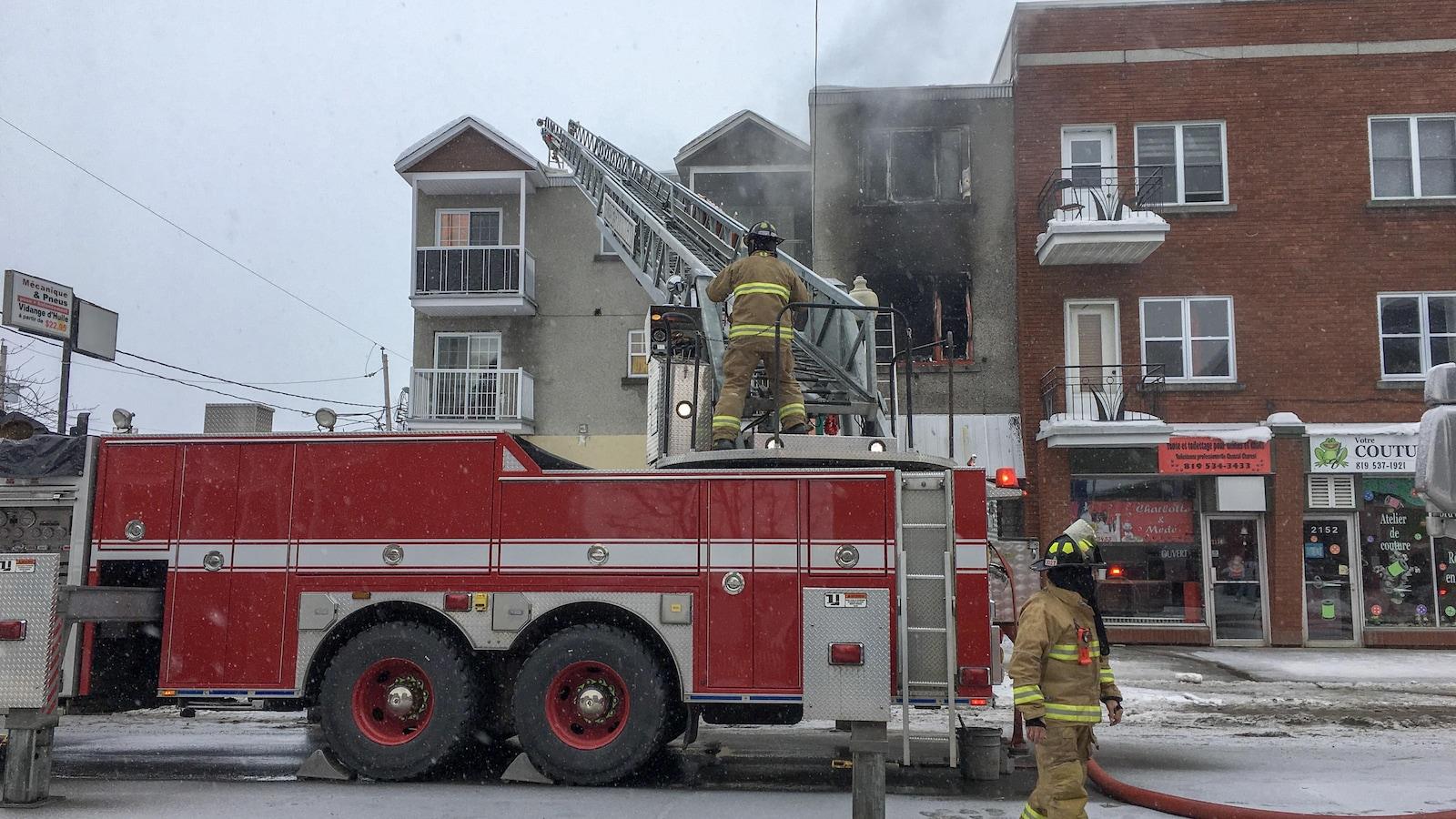 Un camion de pompiers et deux pompiers devant un immeuble.