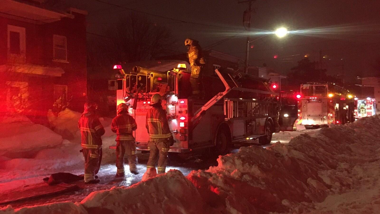 Trois pompiers s'affairent devant leur camion.