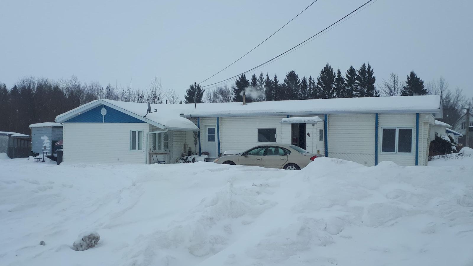 Une maison mobile devant laquelle est stationnée une voiture.