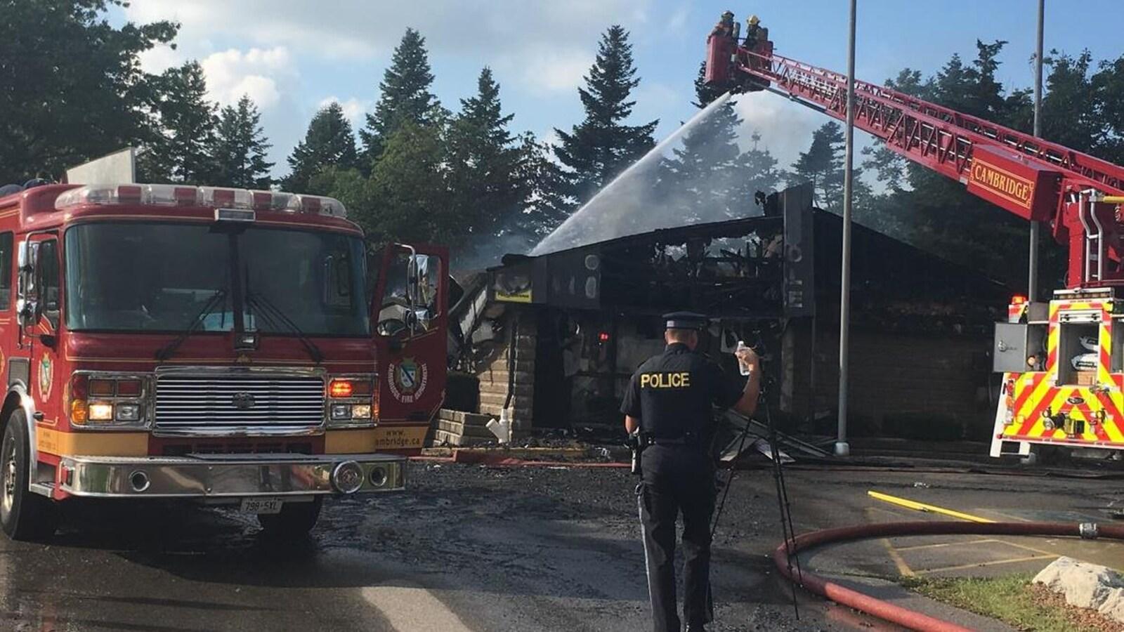 Un camion de pompier arrose les décombres calcinés d'un édifice. On aperçoit un policier à l'avant.