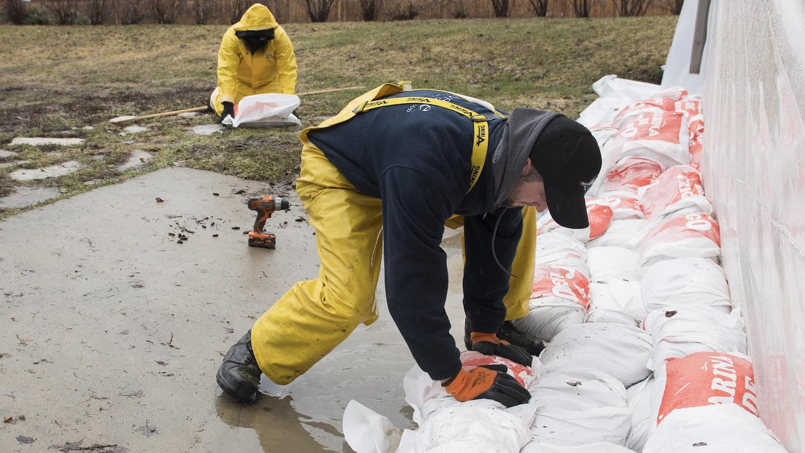 Un homme pose un sac de sable à côté de la fondation d'une maison dans la ville de Hudson, à l'ouest de Montréal, le vendredi 19 avril 2019.