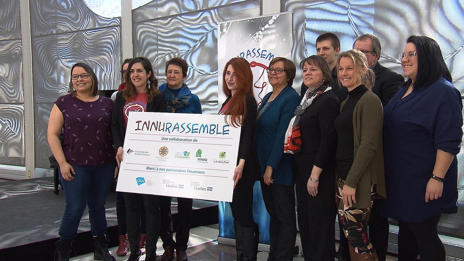 Plusieurs personnes sourient à la caméra avec une affiche d'InnuRassemble