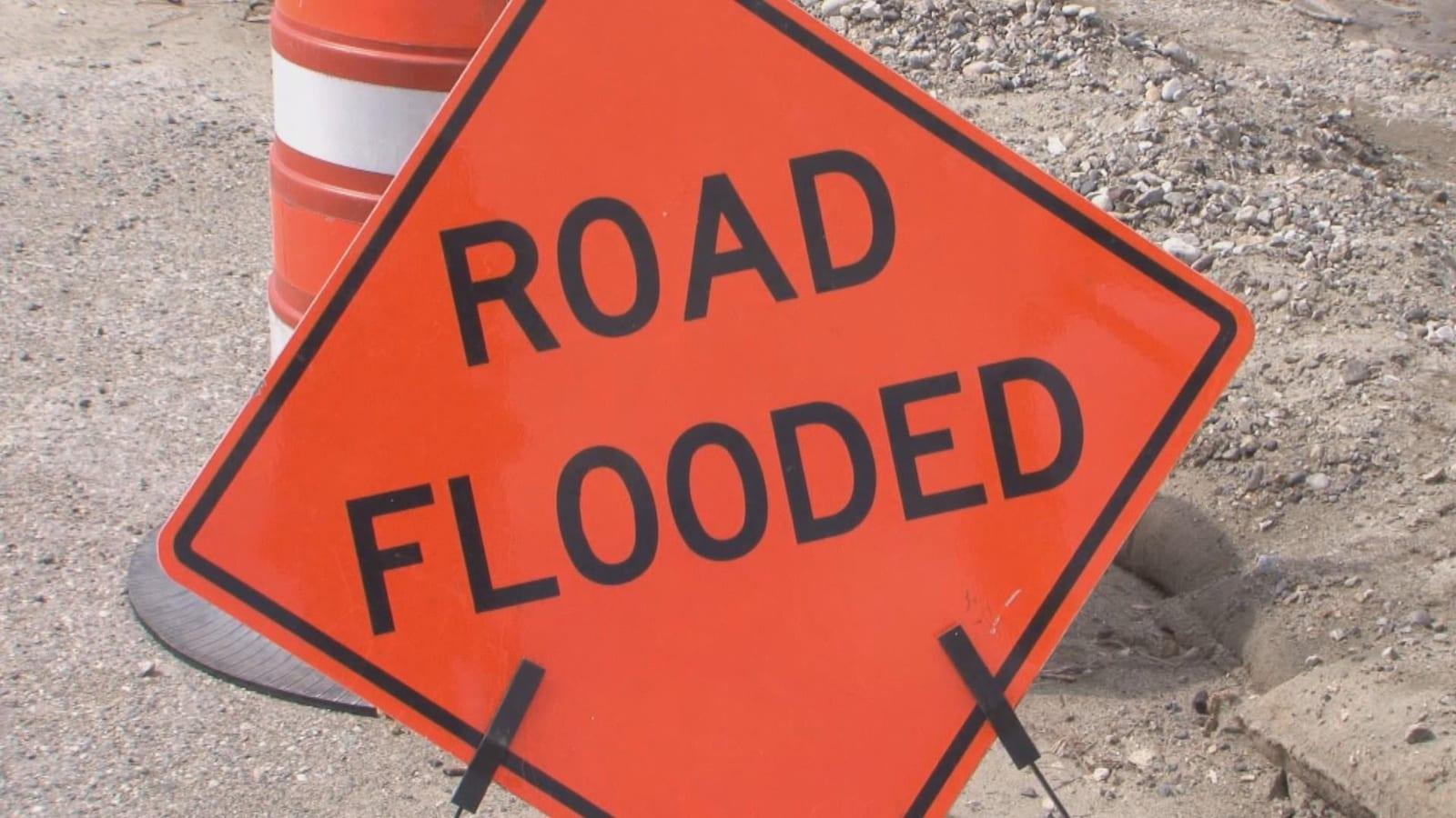 Une pancarte où il est inscrit road flooded, ce qui signifie route inondée.