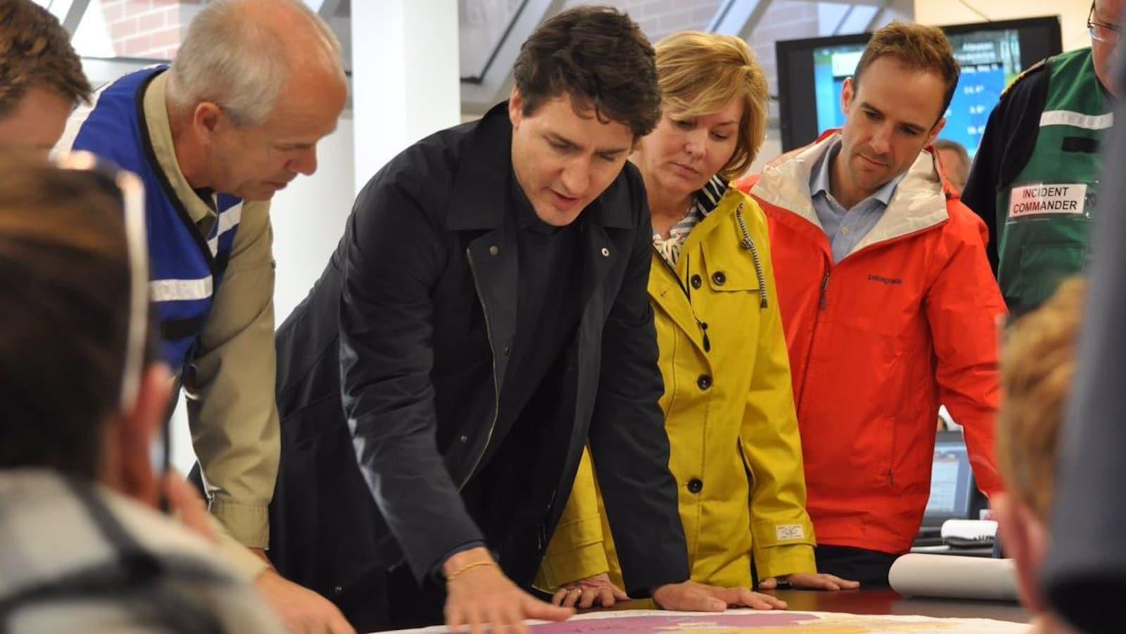 Le premier ministre du Canada, Justin Trudeau, et des pompiers du Nouveau-Brunswick regardent une carte.