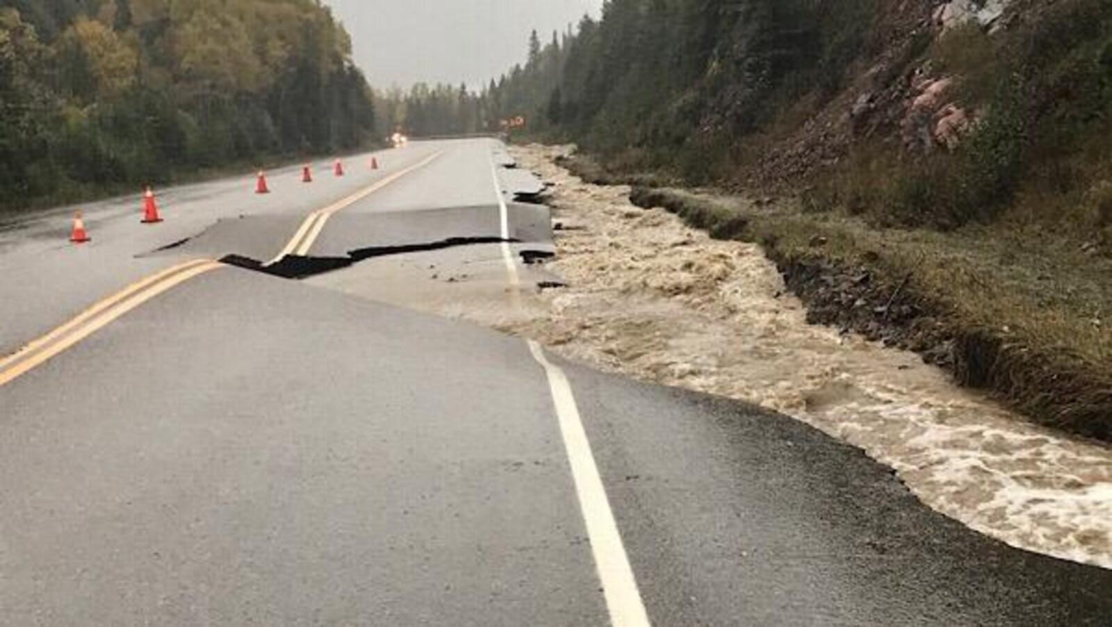 Une route affaissée avec beaucoup d'eau en bordure.