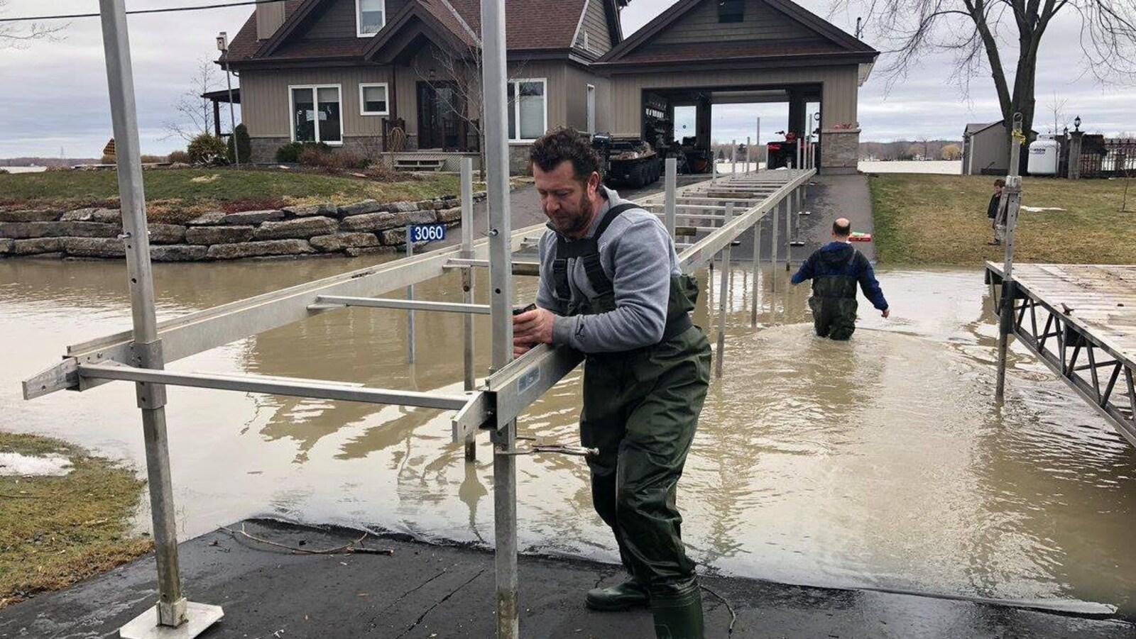 Deux hommes construisent un pont alors qu'ils ont de l'eau aux genoux.
