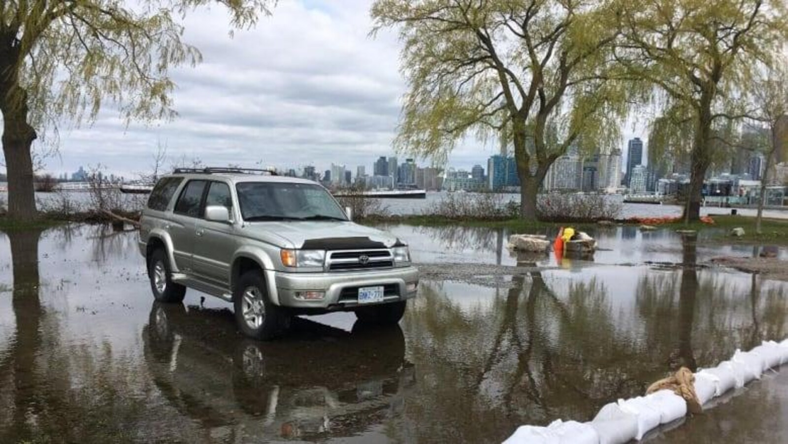 L'eau atteint un véhicule stationné près de la rive.