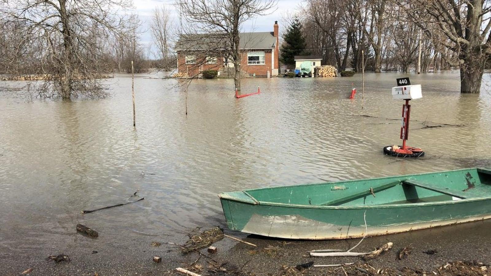 Une chaloupe se trouve devant une maison inondée de Maskinongé.