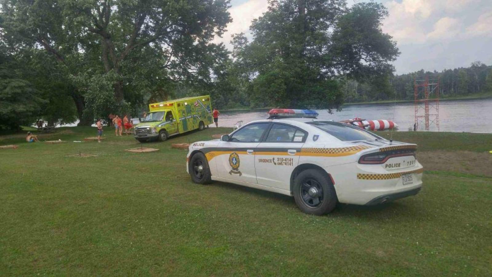 Une voiture de police et une ambulance stationnée en bordure d'un cours d'eau, où se trouvent des plaisanciers. (Archives)