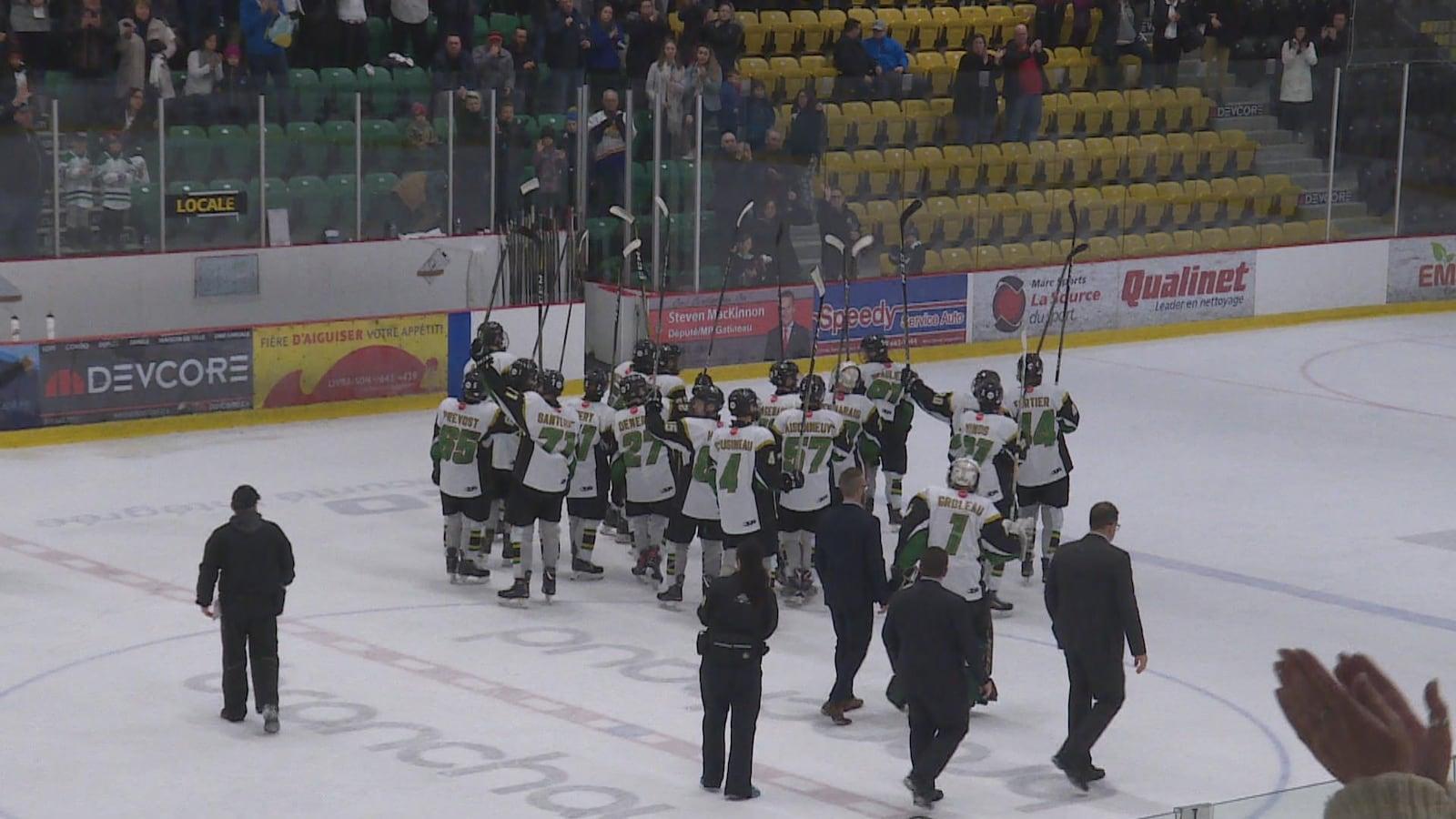 Des joueurs de hockey saluent la foule avec leur bâton.