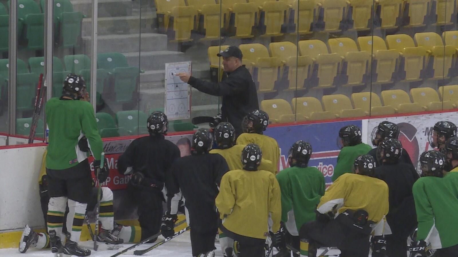 Un homme dessine sur un tableau blanc devant des joueurs de hockey agenouillés.