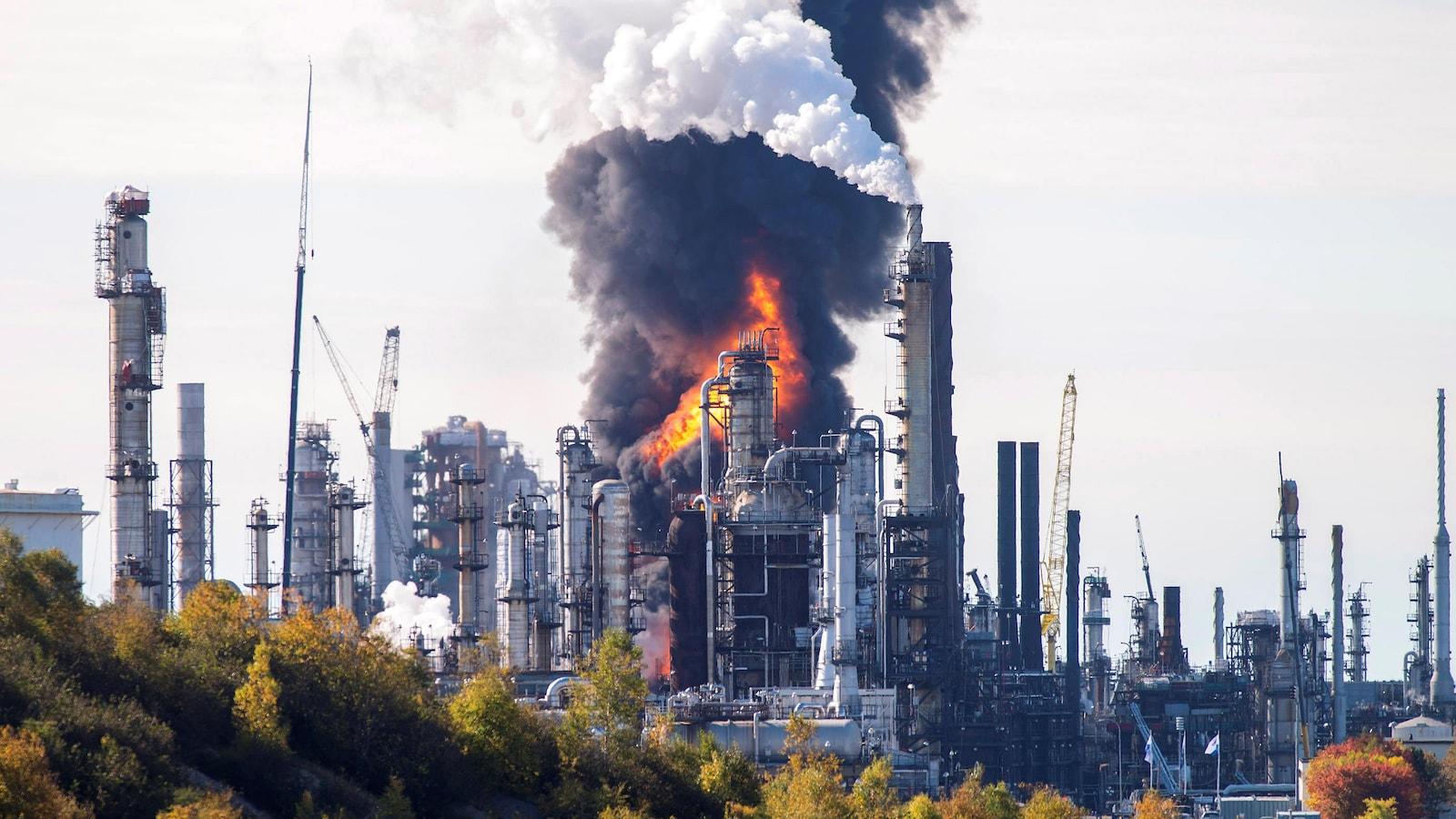 Un incendie est vu au loin, derrière des bâtiments et une colonne de fumée noire s'élève dans le ciel.