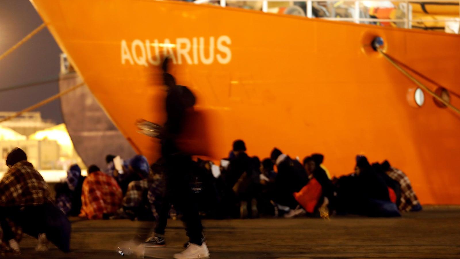 Des gens sont assis dans un port, un énorme bateau orange est amarré près d'eux.