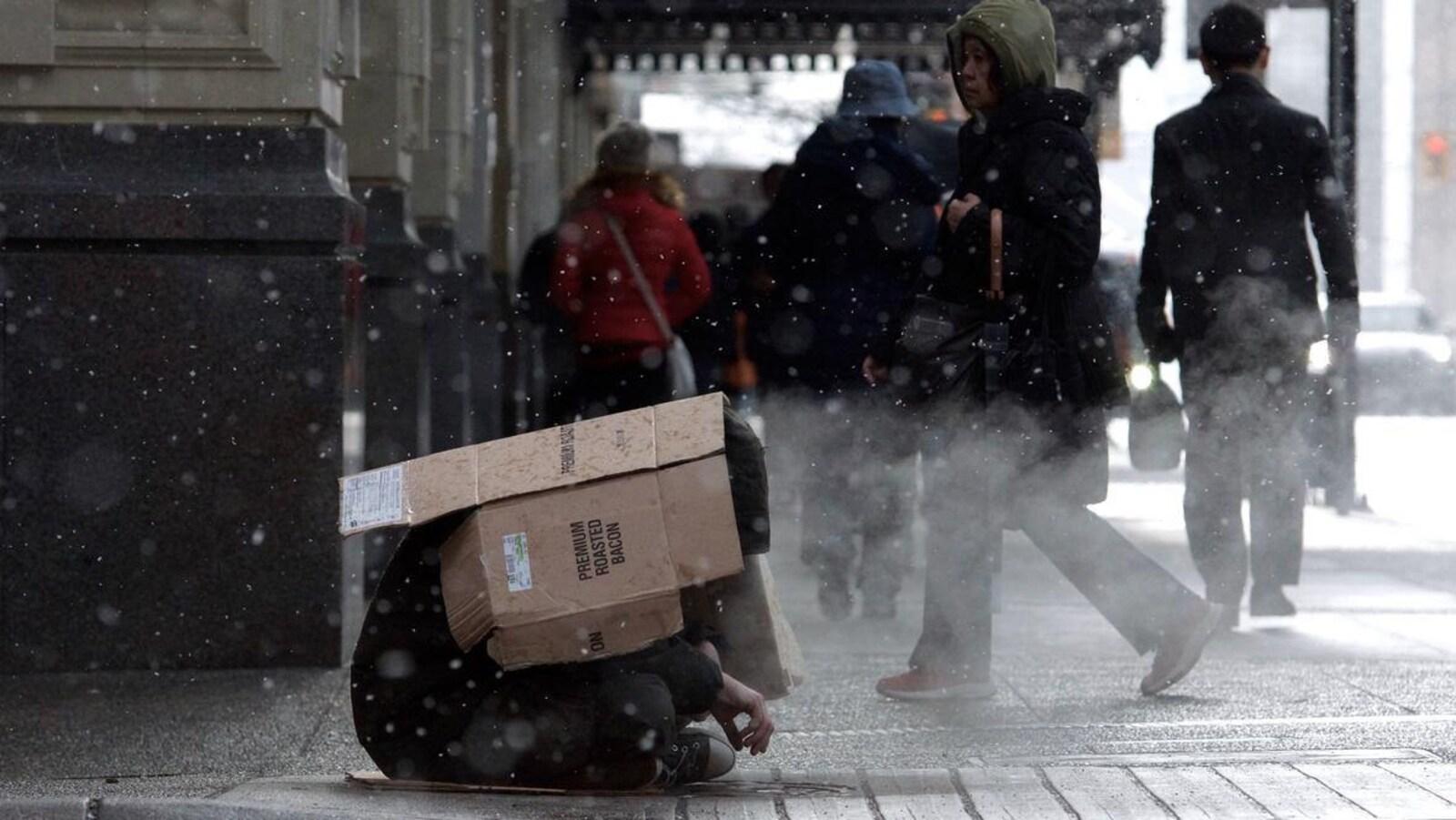 Un sans-abri assis dans le rue, avec des passants en arrière-plan