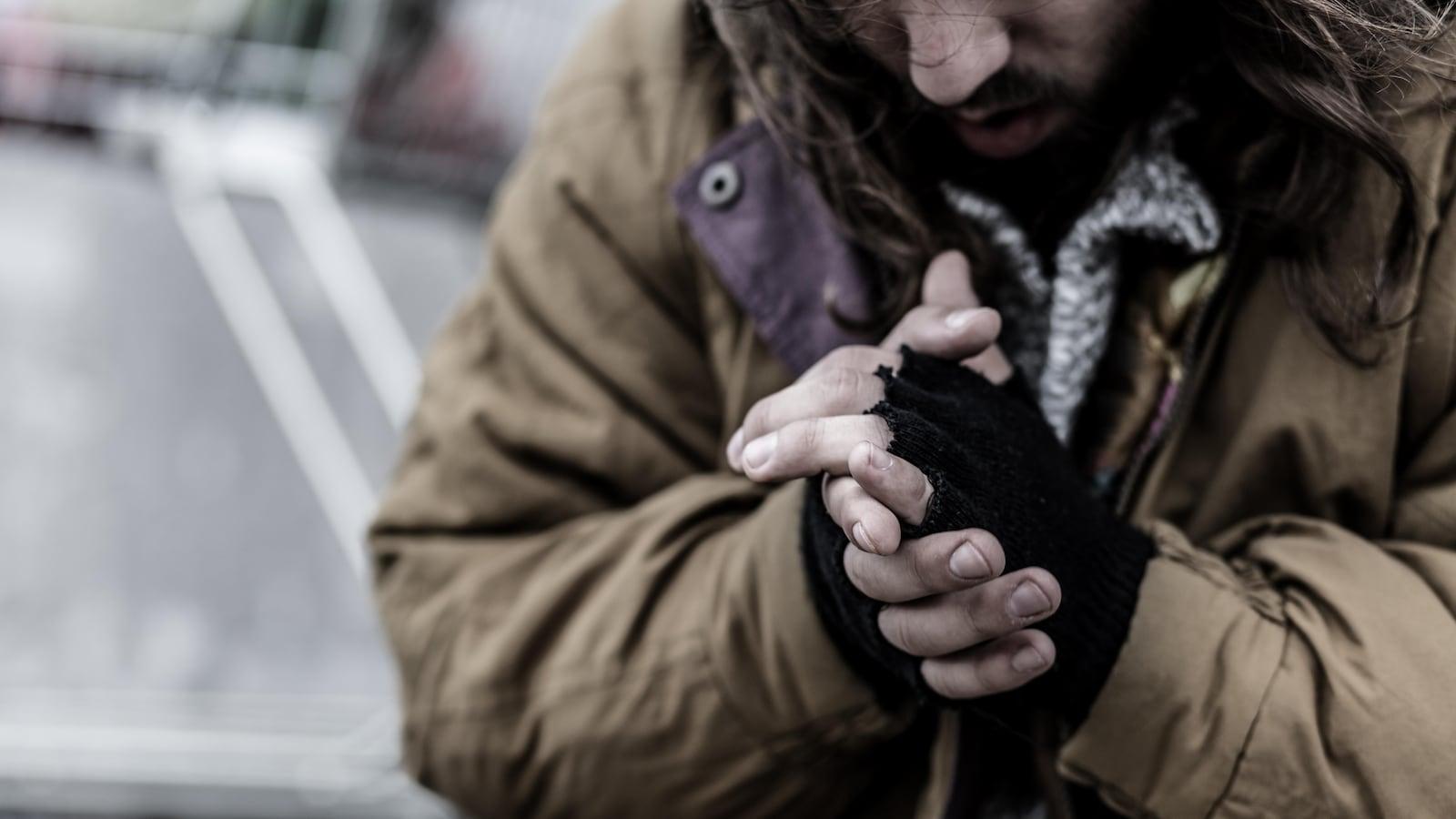 Un homme sur un trottoir se frotte les mains pour se réchauffer.