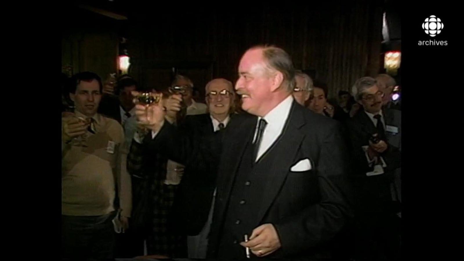 Jacques Parizeau, entouré de militants péquistes, célébrant avec une coupe de champagne à la main et une cigarette dans l'autre.