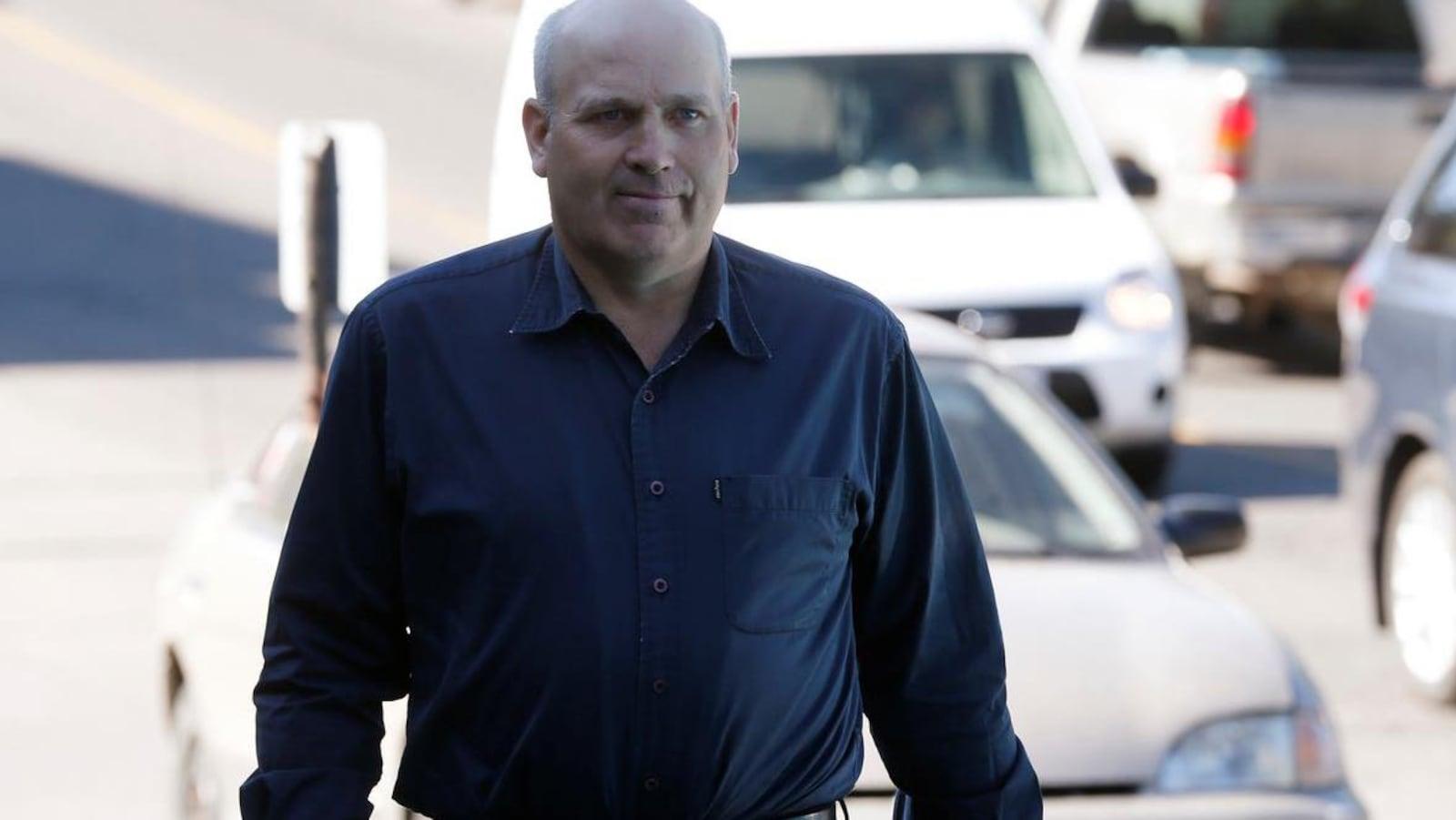 Un homme en chemise marche, avec des voitures en arrière-plan.