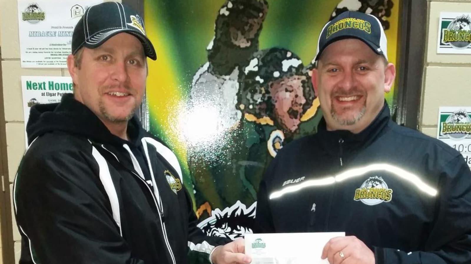 Jamie Brockman tient un chèque destiné aux Broncos de Humboldt, que lui donne Kelsey Lindal.