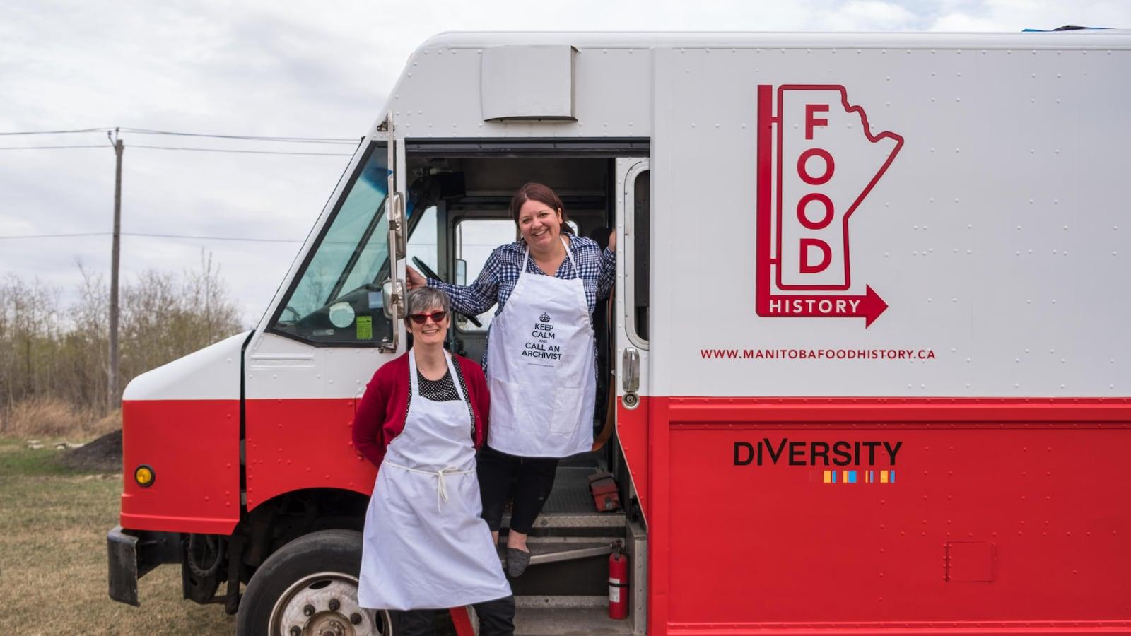 Deux femmes posent devant un camion restaurant repeint en blanc et rouge et sur lequel on lit Manitoba Food History.