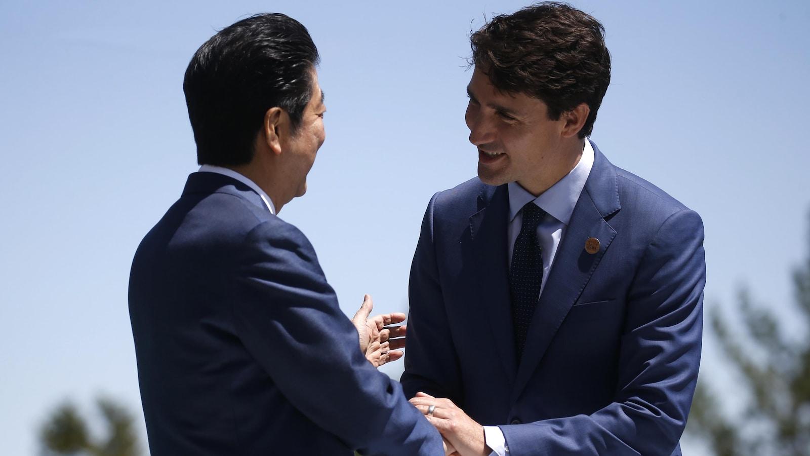 Deux hommes se serrent chaleureusement la main à l'extérieur.