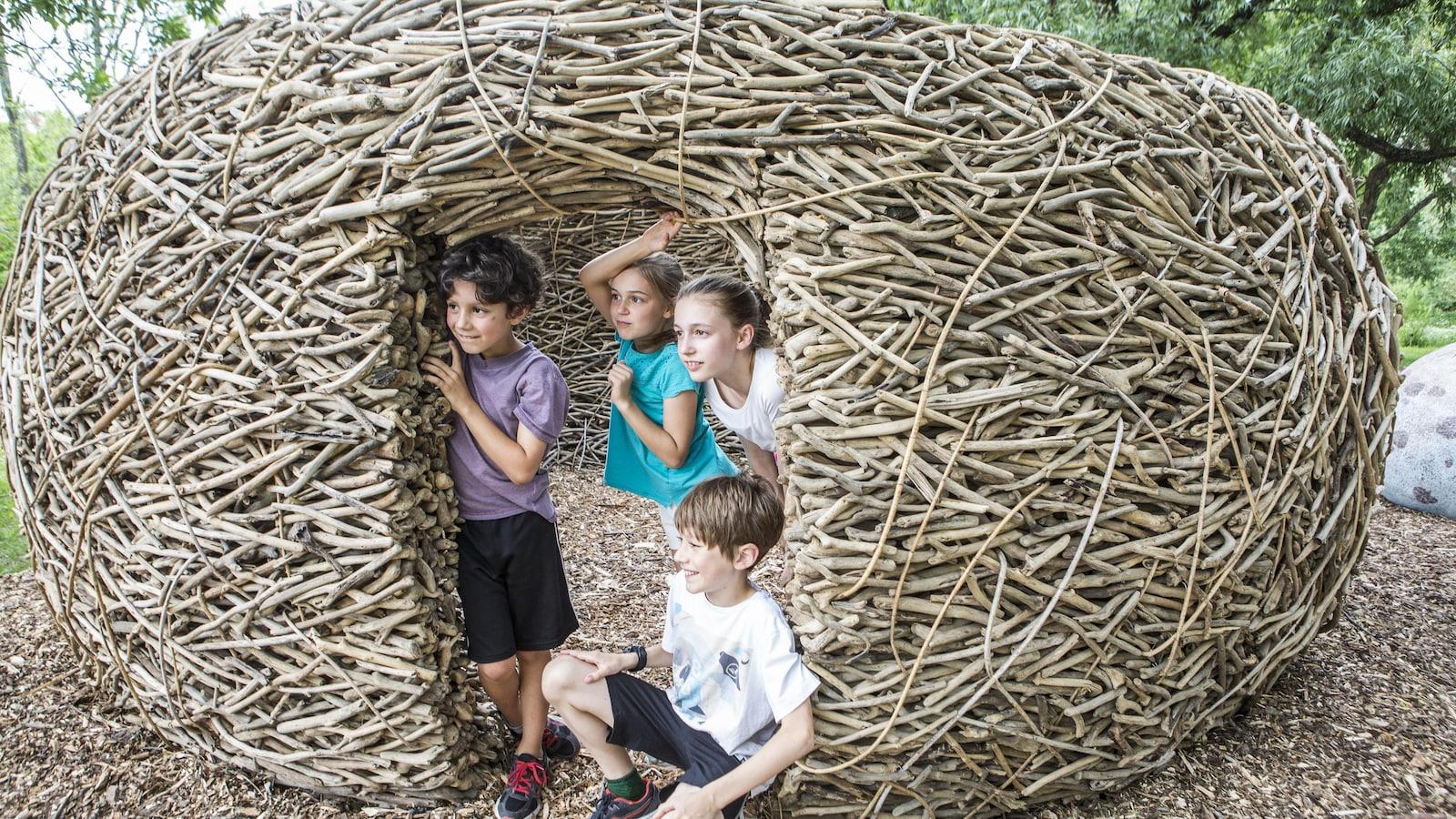 Quatre enfants visitent un abri d'insecte à l'exposition