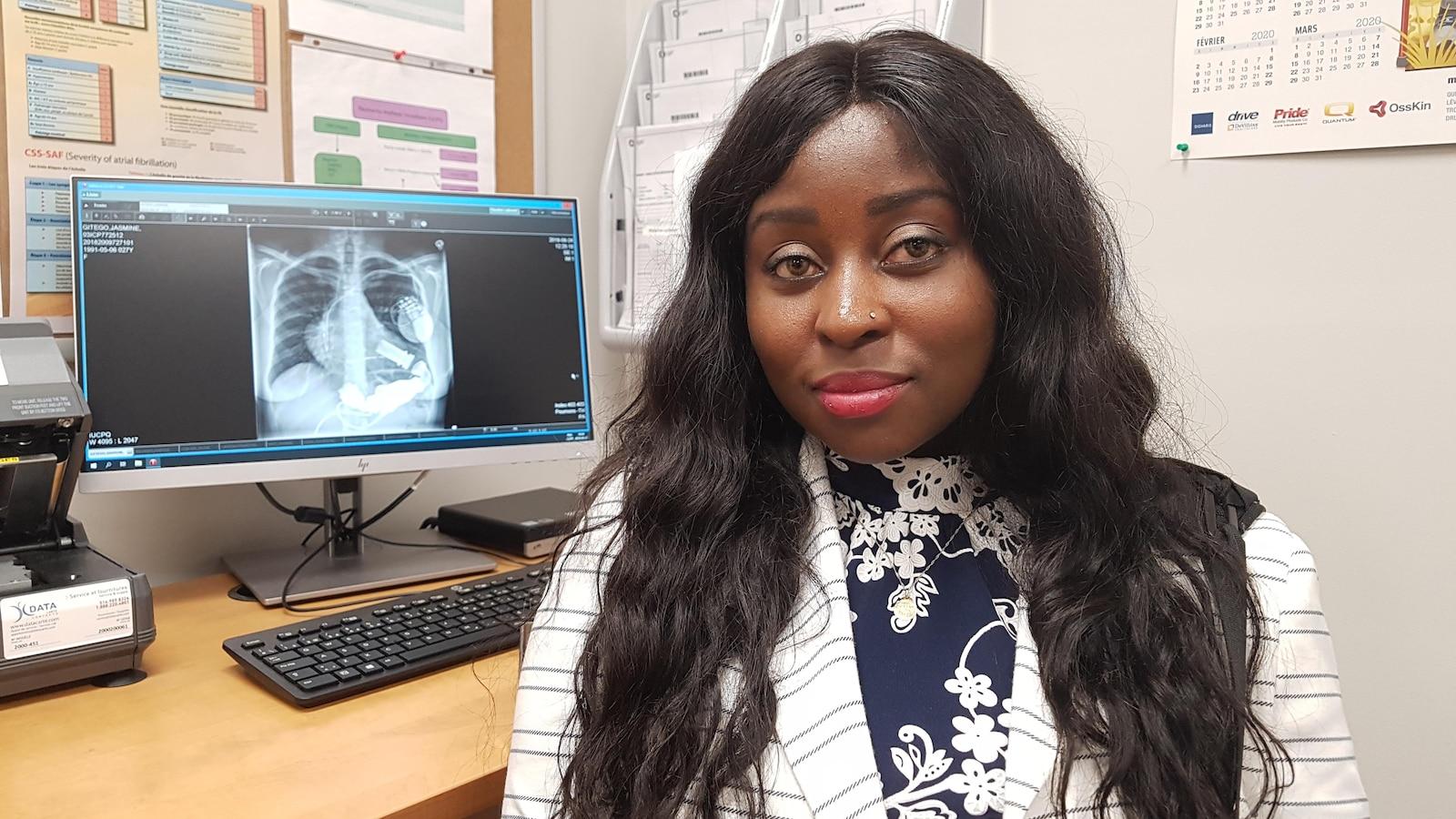 Jasmine Gitego assise devant l'écran de l'ordinateur où la radiographie de sa poitrine montre le cœur mécanique.