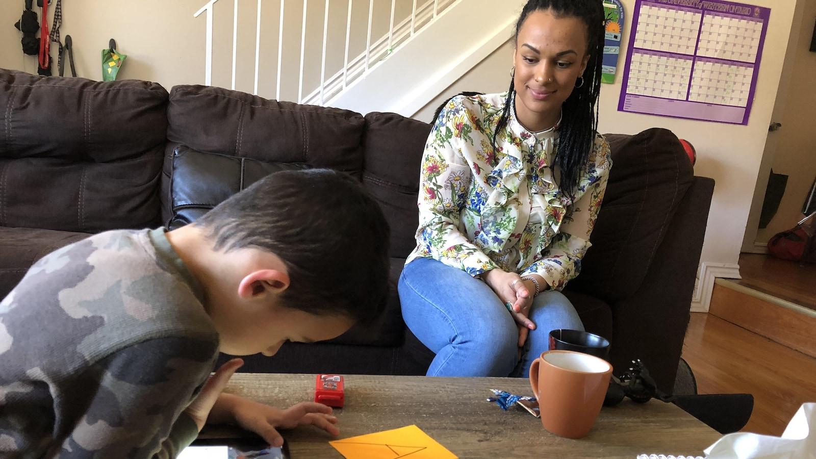 Dans un salon, une femme assise sur un divan observe son fils qui joue sur un ipad.