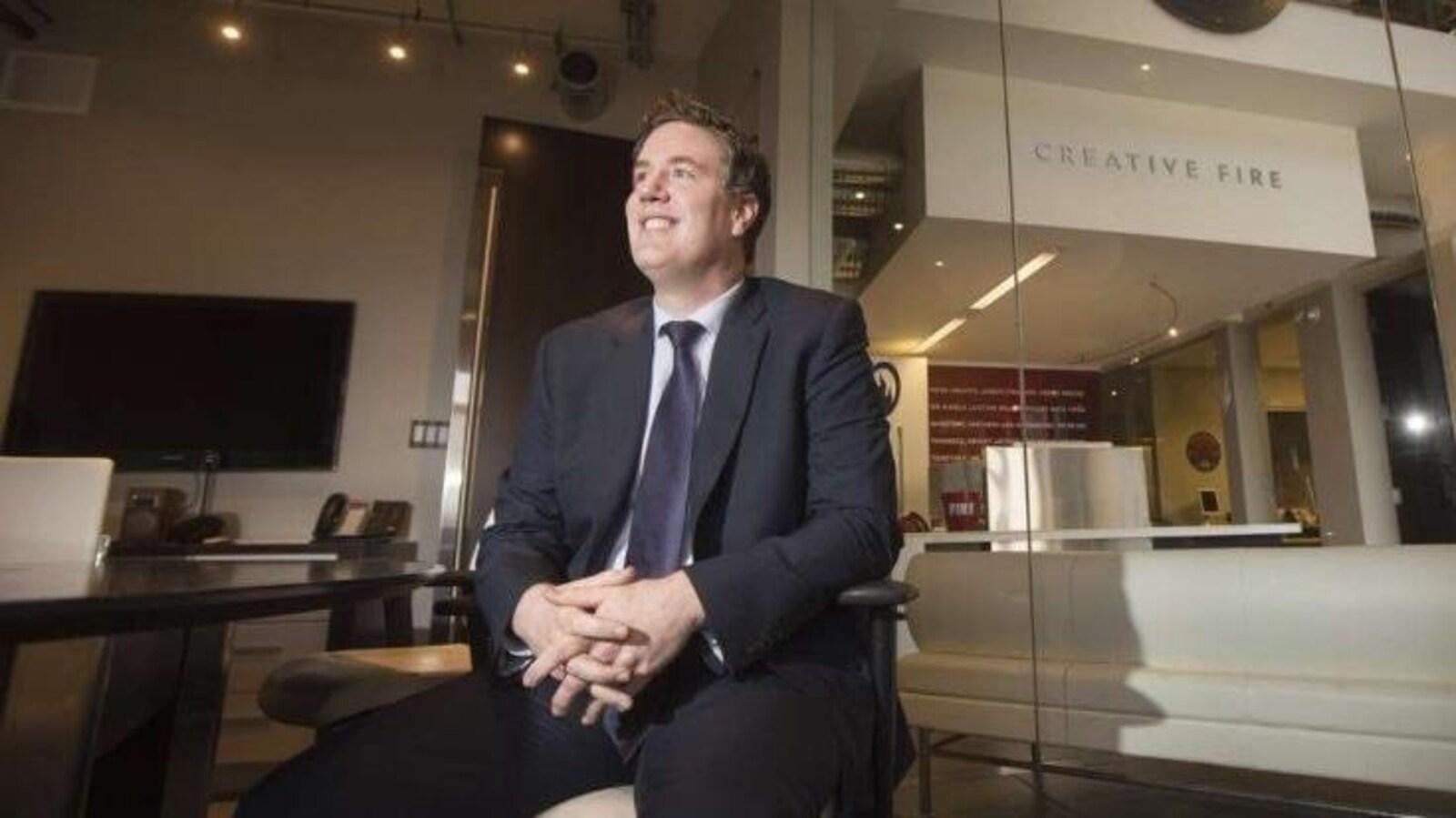 Un homme  photographié en contre-plongée, en costume cravate et assis dans un bureau au design moderne, sourit en regardant vers une lumière devant lui. Derrière lui se trouve une baie vitrée donnant sur l'intérieur des locaux de l'entreprise Creative Fire.