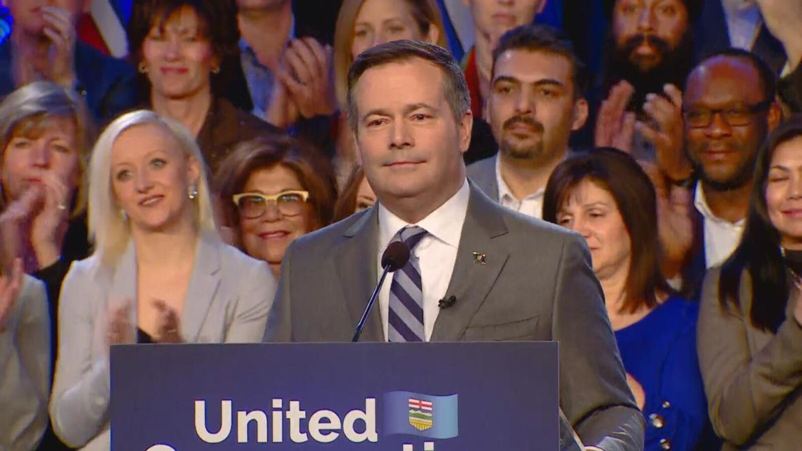 Avec de nombreux supporteurs derrière lui, Jason Kenney qui porte un costume-cravate se tient devant un podium.