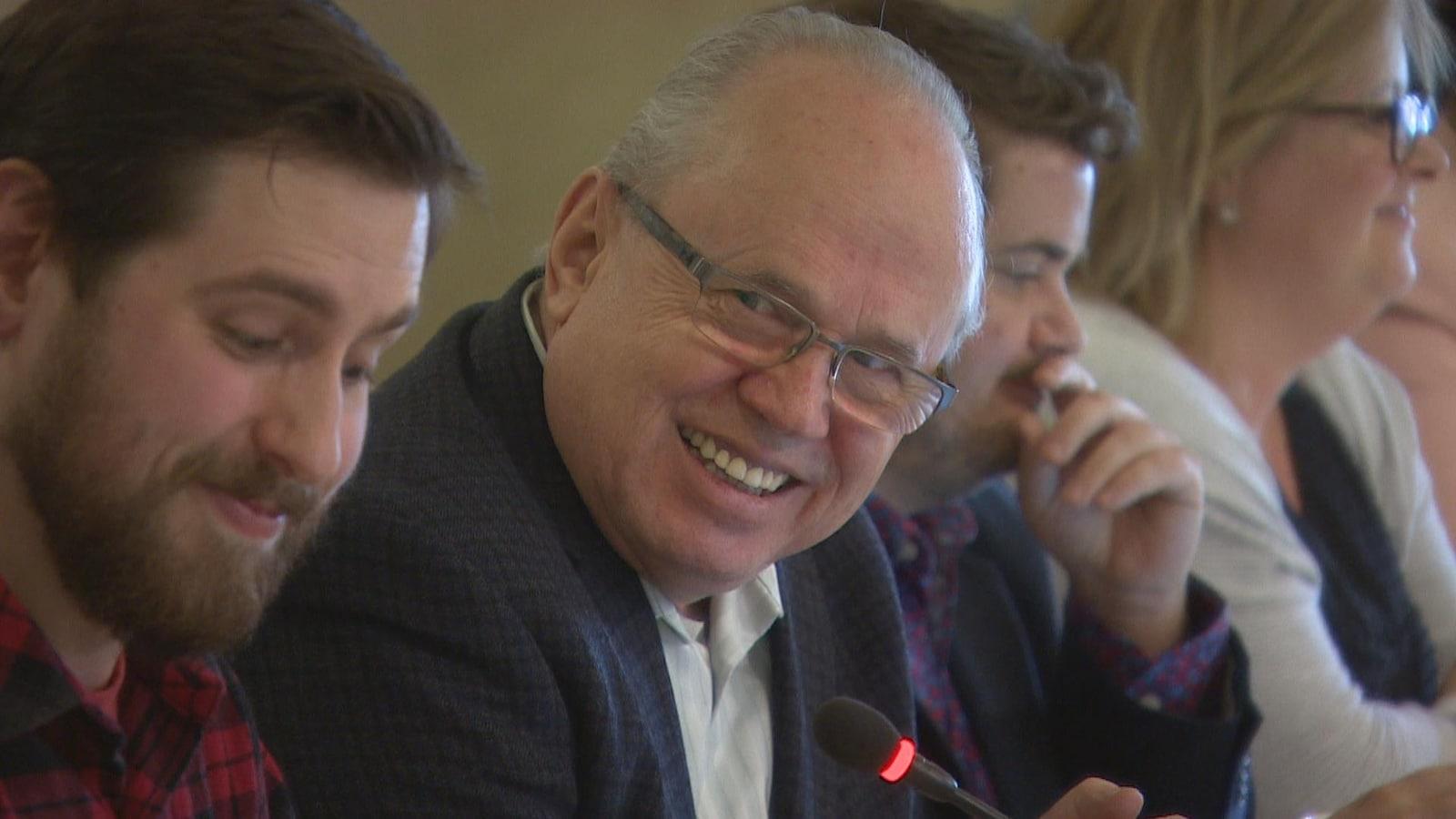 Gros plan sur Jean Johnson, au centre, un homme à lunettes souriant, aux côtés d'autres membres de la FCFA, assis dans une salle de conférence.
