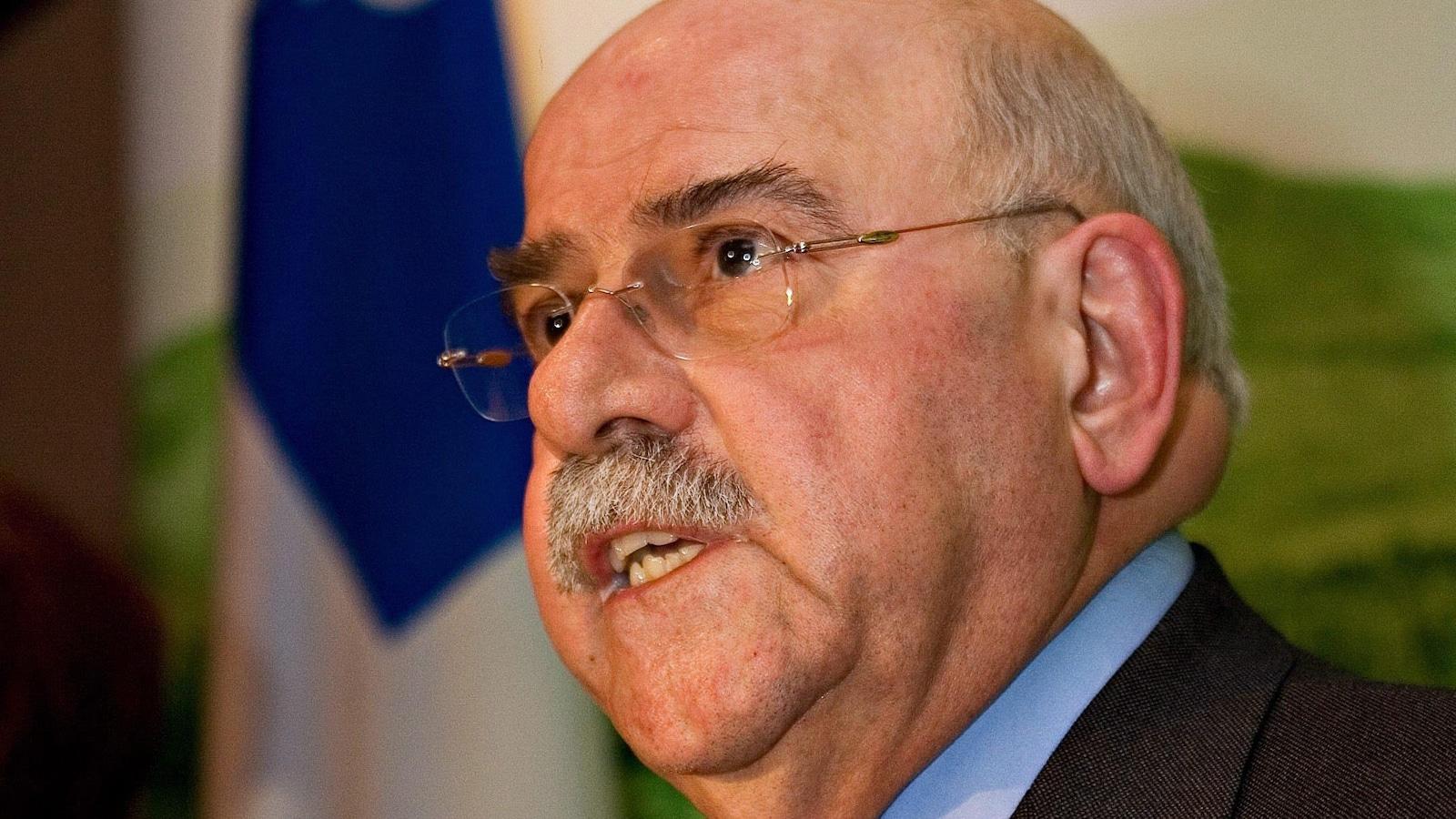 Un homme moustachu qui porte des lunettes s'exprime lors d'une conférence de presse.