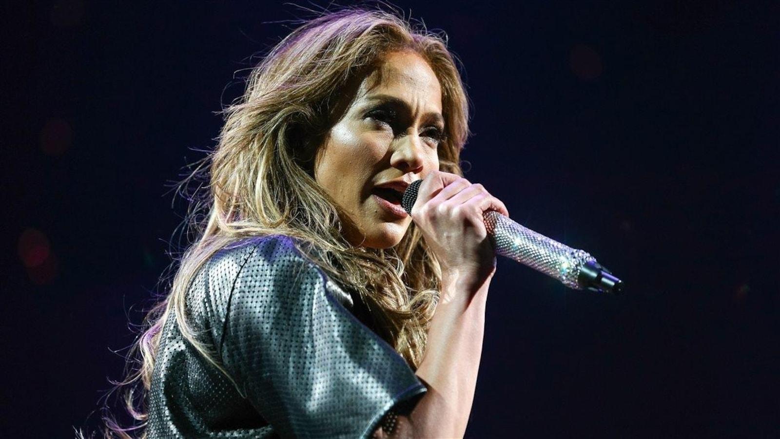 Jennifer Lopez chante avec un micro dans la main.