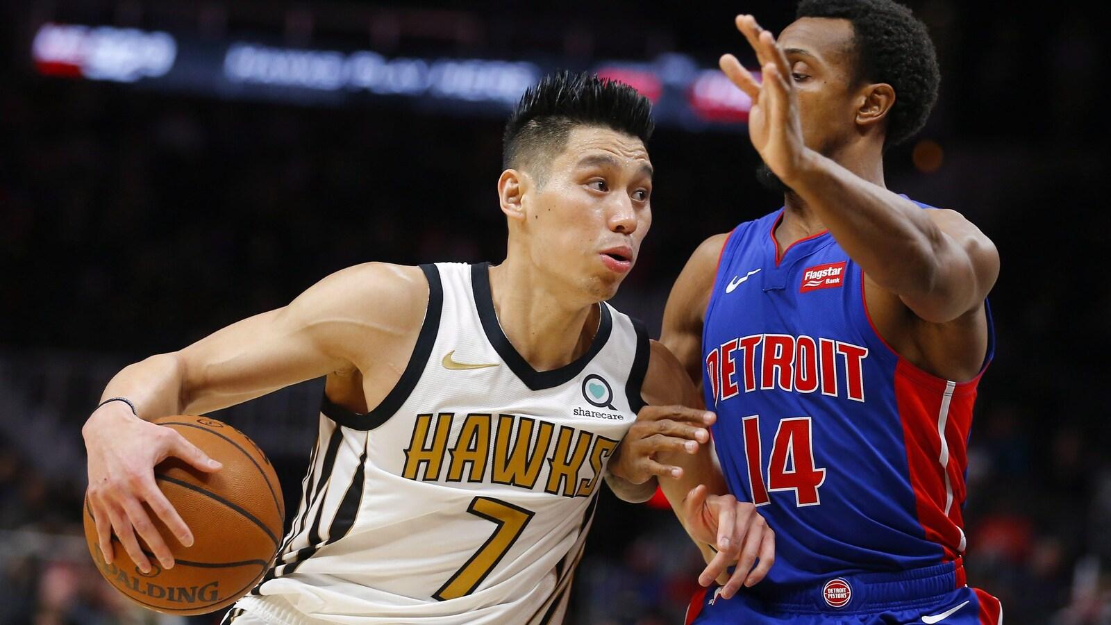 Un joueur de basketball en contourne un autre avec le ballon.