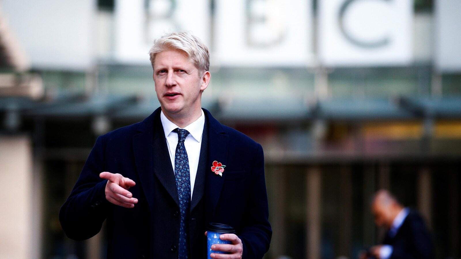Jo Johnson quitte les bureaux de la BBC, café à la main.