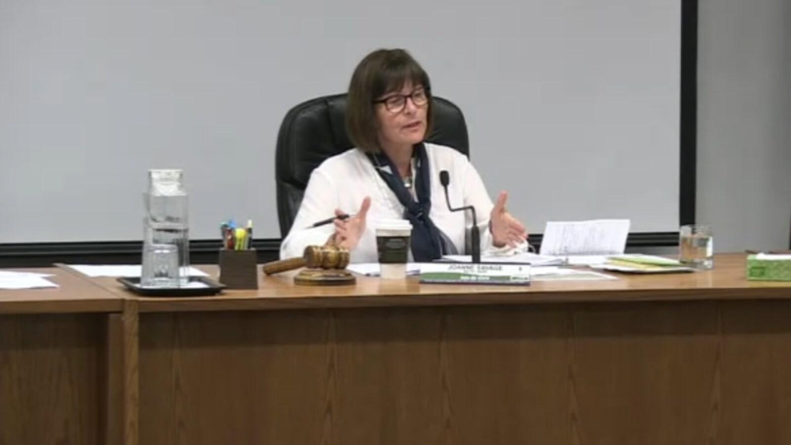 La mairesse de Nipissing Ouest assise à une table pendant une réunion du conseil municipal.