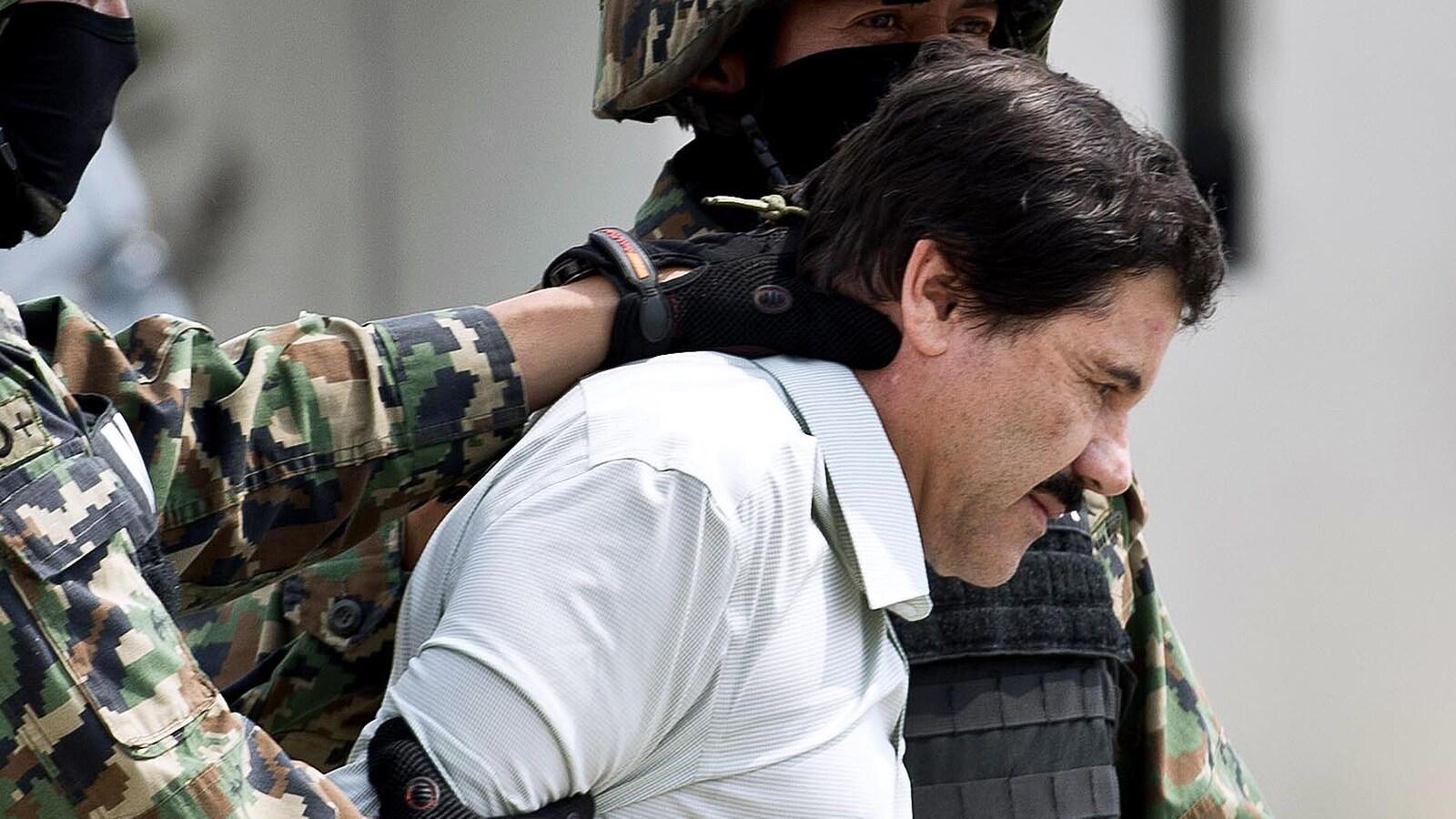 Deux soldats flanquent Joaquin El Chapo Guzman qui apparait en chemise blanche, la tête légèrement penchée vers le bas.